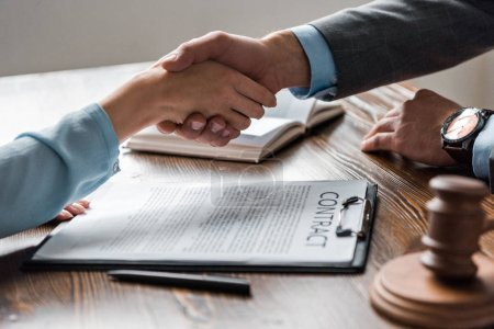 Photo pour Photo recadrée de l'avocat et son client se serrant la main au-dessus du contrat - image libre de droit
