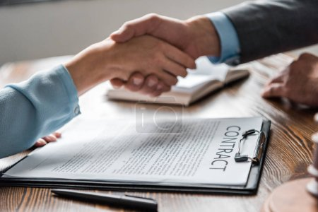 close-up view of clipboard with contract and lawyer with client shaking hands behind