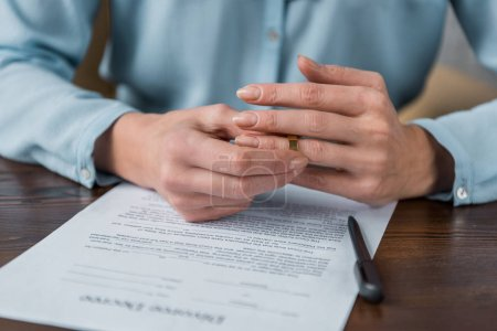 cropped shot of woman taking off wedding ring and divorce decree on table