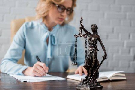 Photo pour Vue rapprochée de Dame justice statue et femme juge travaillant derrière - image libre de droit