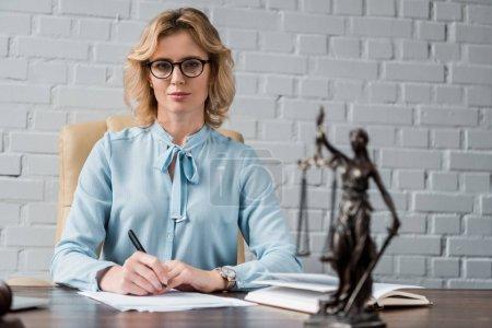 Photo pour Confiant femme avocate à lunettes assis au milieu de travail et en regardant la caméra - image libre de droit