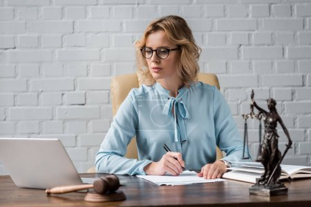 Photo for Serious female judge in eyeglasses working with papers and using laptop at workplace - Royalty Free Image
