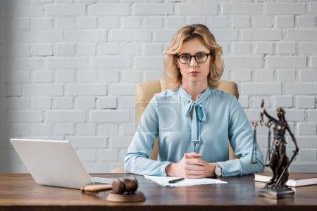 Photo pour Avocate sérieuse dans les lunettes assis sur le lieu de travail et regardant la caméra - image libre de droit