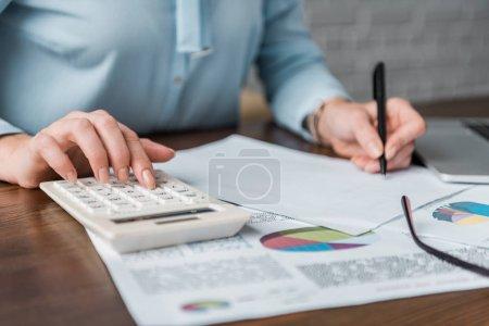 Photo pour Plan recadré de femme d'affaires en utilisant une calculatrice et en travaillant avec des papiers - image libre de droit