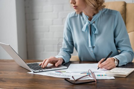 cropped shot of focused businesswoman working with papers and laptop in office