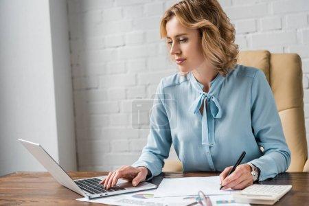 Photo pour Belle femme d'affaires travaillant avec les papiers et ordinateur portable au bureau - image libre de droit