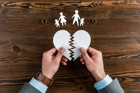 cropped shot of man holding teared heart with family and engagement rings on wooden table, divorce concept