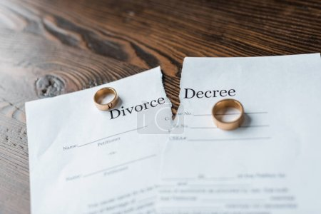close-up shot of teared divorce decree and engagement rings on wooden surface