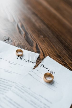 close-up shot of teared divorce decree and engagement rings on wooden tabletop