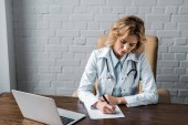 confident female doctor writing document at workplace in office