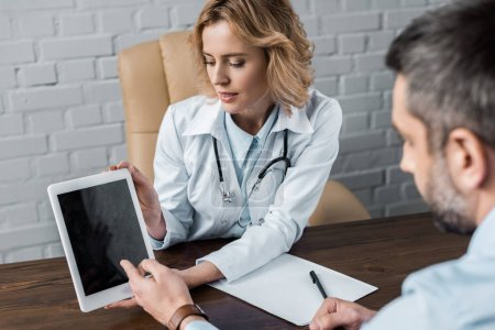 attractive female doctor showing tablet with blank screen to patient at office