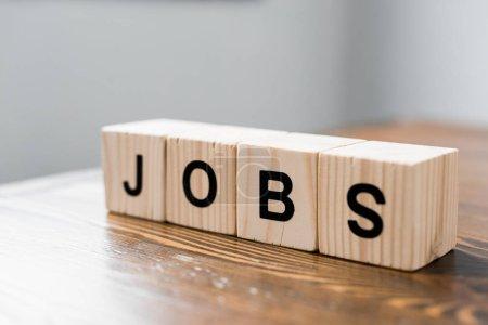 Foto de Primer plano de cubos de madera con el cartel de JOBS en la mesa - Imagen libre de derechos