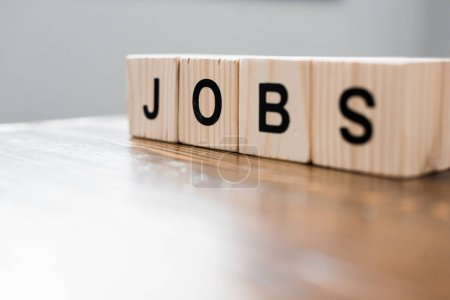 close-up shot of wooden blocks with JOBS sign on table