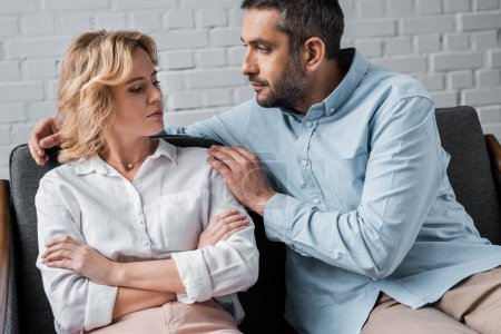 man talking to wife while sitting on couch after quarrel