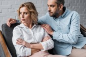man talking to depressed wife while sitting on couch after argument