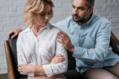 man talking to depressed wife while sitting on couch after quarrel