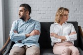 mad couple sitting on couch after quarrel and looking away