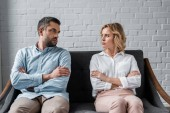 couple sitting on couch after quarrel and looking at each other