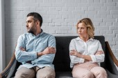 angry couple sitting on couch after quarrel and looking away