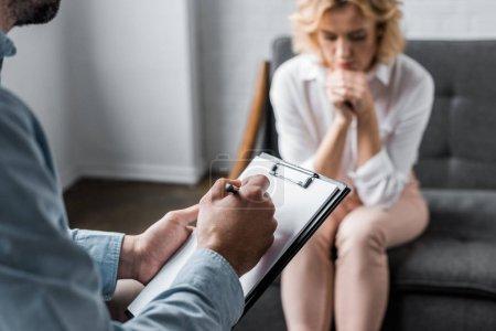 Photo pour Femme dépressive ayant séance de thérapie de psychologue à l'office et le thérapeute écrit dans le presse-papiers - image libre de droit