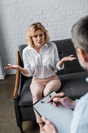 emotional woman on psychologist therapy session at office