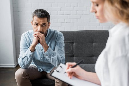 sad adult man on psychologist therapy session at office