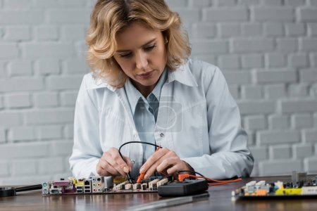 female computer engineer with tester examining motherboard