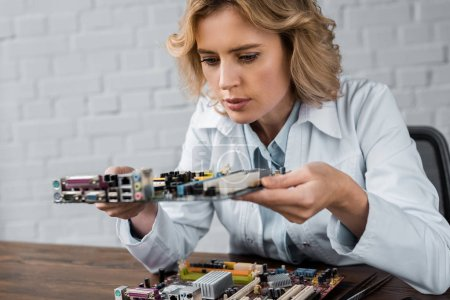 concentrated female computer engineer holding motherboard