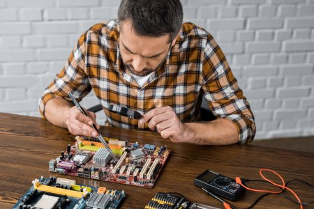 concentrated electronics engineer with tweezers and magnifying glass repairing motherboard