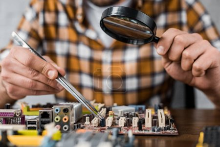 Photo for Cropped shot of computer engineer with tweezers and magnifying glass repairing motherboard - Royalty Free Image