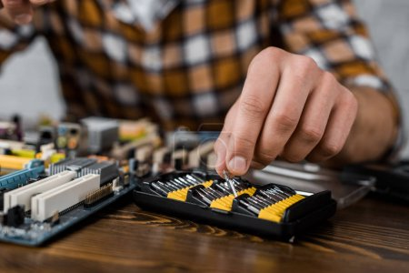 computer engineer taking screwdriver caps to repair motherboard