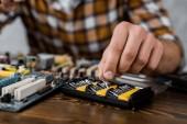 computer engineer taking screwdriver caps to repair motherboard