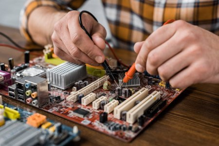 Photo for Cropped shot of computer engineer with tester examining motherboard - Royalty Free Image