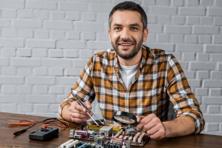 handsome smiling computer engineer with tweezers and magnifying glass repairing motherboard