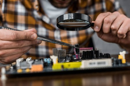 cropped shot of electronics engineer with tweezers and magnifying glass repairing motherboard