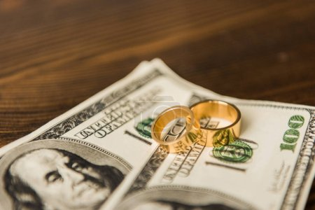 close-up shot of cash and wedding rings on wooden table