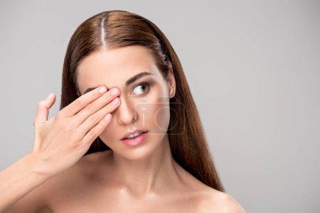 portrait of beautiful brunette girl closing one eye, isolated on grey