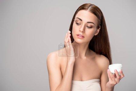 Photo pour Jeune femme en appliquant la crème pour le visage sur une peau parfaite, isolée sur fond gris - image libre de droit