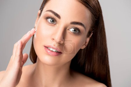 beautiful woman applying anti-wrinkle cream on face, isolated on grey