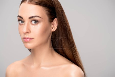 attractive nude girl with eye cream on face, isolated on grey