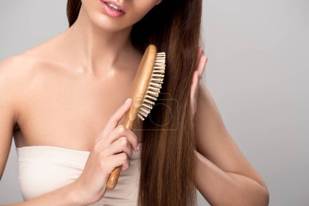 cropped view of woman combing hair with wooden hairbrush, isolated on grey