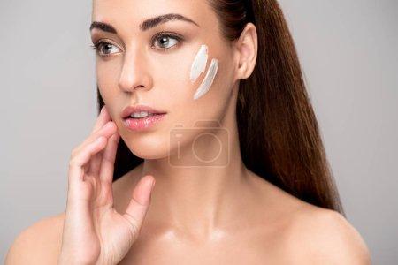 Photo pour Jolie jeune femme appliquant de la crème sur le visage, isolée sur le gris - image libre de droit