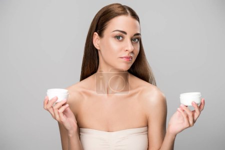 beautiful young woman choosing face cream, isolated on grey