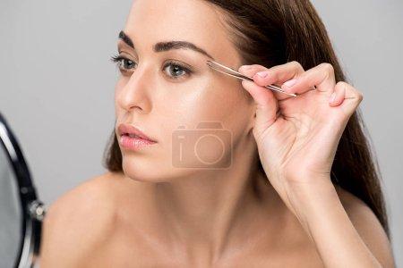 beautiful young woman correcting shape of eyebrows with tweezers isolated on grey