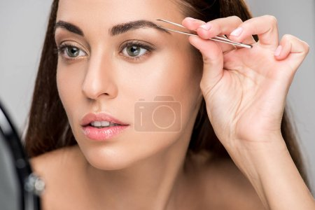 Photo for Attractive woman correcting shape of eyebrows with tweezers isolated on grey - Royalty Free Image