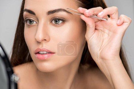 attractive woman correcting shape of eyebrows with tweezers isolated on grey