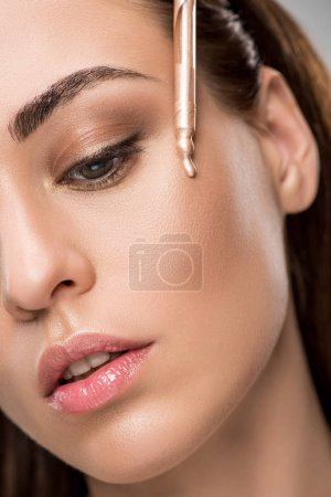 attractive girl applying highlighter or bronzer with pipette