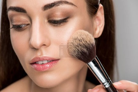 attractive girl applying powder on face with cosmetic brush