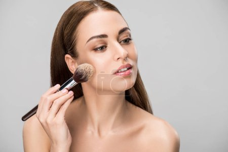 beautiful girl applying face powder with cosmetic brush, isolated on grey