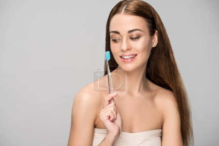 Photo for Attractive smiling woman holding toothbrush isolated on grey - Royalty Free Image